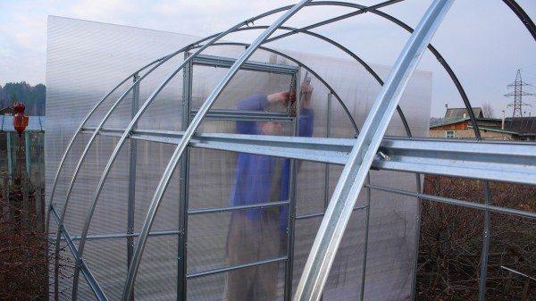 Процесс укладки листа поликарбоната на алюминиевый каркас.