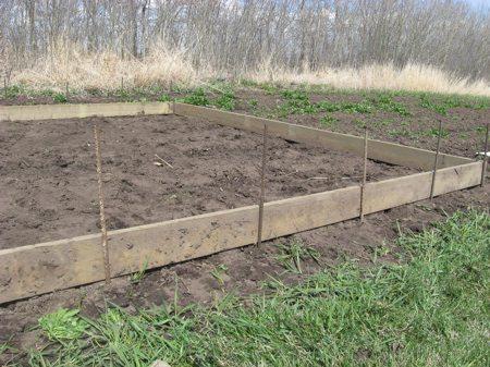 Воткните арматуру в землю для крепления дуг