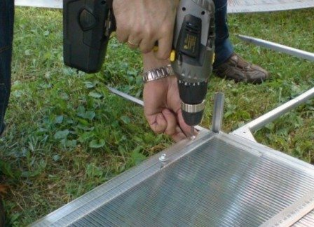 На фото запечатлен процесс крепления поликарбоната к каркасу.